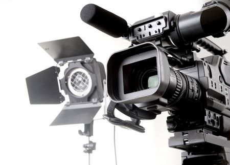 video camera: isolated digital video camera recorder on tripod  and spot light with white background