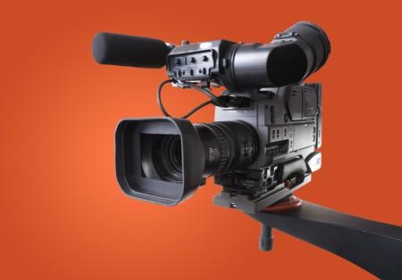 black dv-cam camera recorder on tv crane with orange background