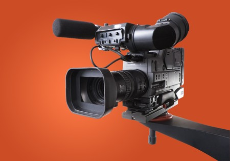 black dv-cam camera recorder on tv crane with orange background