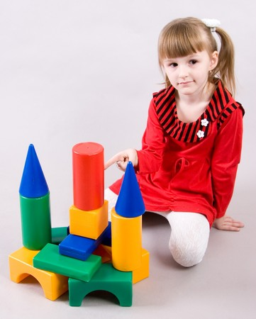 little girl build tower from multicoloured toy bricks photo