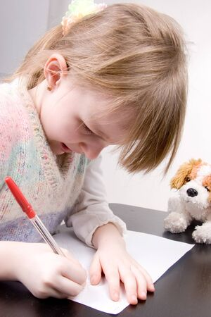 the little girl drawing with red pen at white paper photo