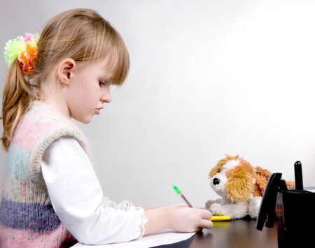 the little girl drawing with green pen at white paper photo