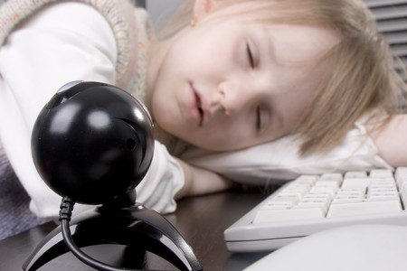 web camera shoot the little girl sleeping at the computer keyboard photo