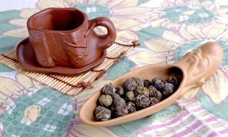 loose leaf: arcilla con cuchara de t� de hojas sueltas y taza de t� Foto de archivo