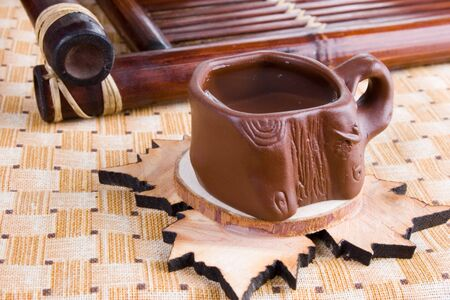 clay cup of tea on wooden hot pad photo