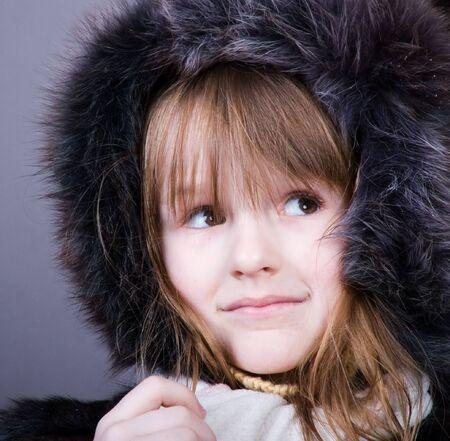 fur hood: studio portrait of little girl in black fur
