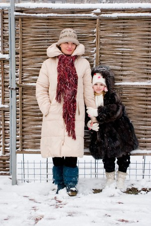 fense: mother and her daughter in winter stay at wicker fense Stock Photo