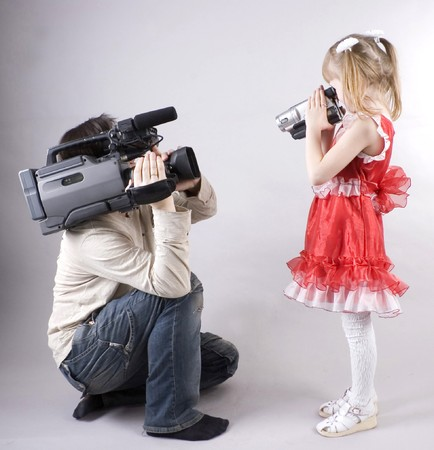 professional cameraman and little girl with home video camera shooting one another