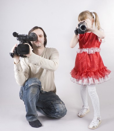 professional cameraman and little girl with home video camera shooting at studio Stock Photo - 4541352