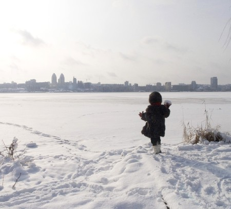little girl look to the city on the far bank of frozen river photo