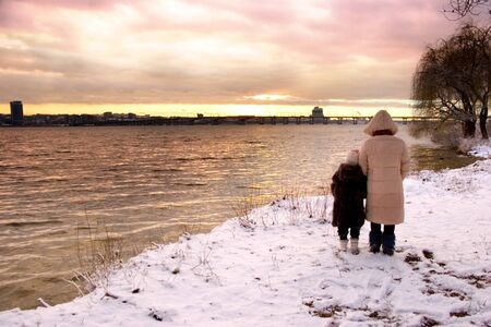mother and dauhgter look at winter sunset over big river photo