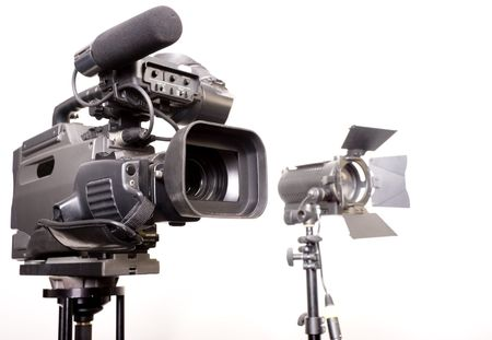 stand dv-cam camcorder and light source in studio