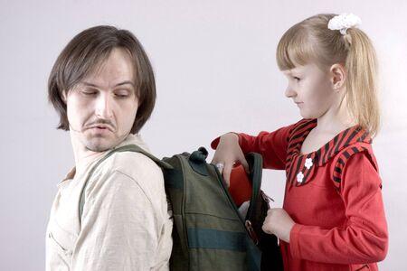knapsack: little girl take something from fathers knapsack