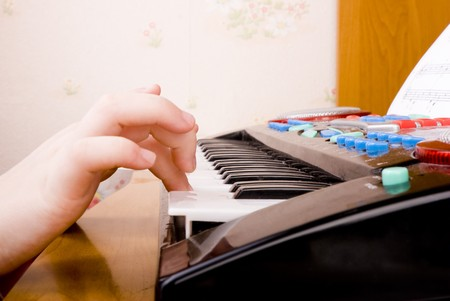 close-up hands of little girl playing at toy musical keyboard Stock Photo - 6981354