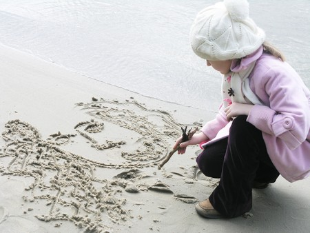 little girl drawing a princess at the sand in riverbank