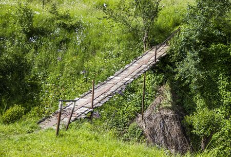 pedestrian bridge: wooden footbridge under the small river Stock Photo