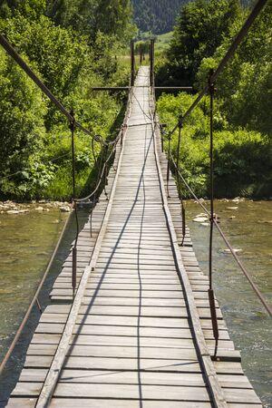 wooden footbridge under the fast river Stock Photo