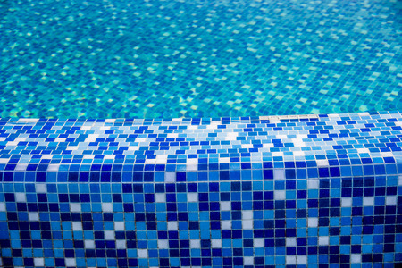 bath: close-up edge of the swimming pool with blue mosaic tiles Stock Photo