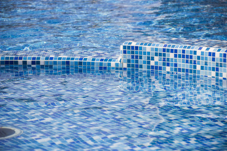 close-up edge of the swimming pool with blue mosaic tiles Stock Photo