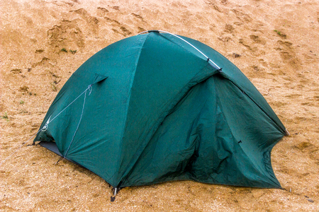 close-up green tourist tent at the sand Stock Photo