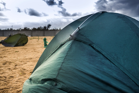 green camping tent on the beach at the stormy weather and broken tent at back Stock Photo