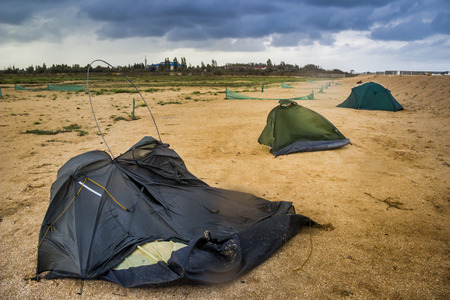 blue broken camping tent on the beach at the stormy weather and good tent at back Stock Photo