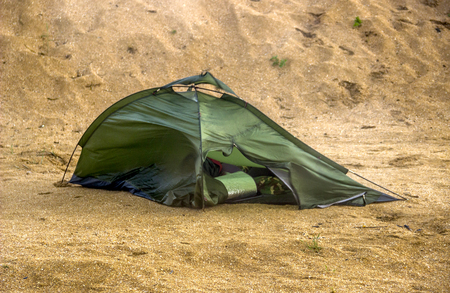 green broken camping tent on the beach at the stormy weather Stock Photo