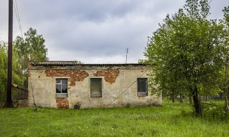 a brick barn in countryside with broken walls and windows