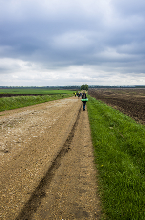 hikers at the rural road through agricultural fields Stock Photo