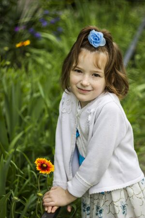 portrait of little girl with blossoming flower of common blanketflower (Gaillardia aristata)