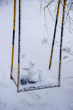 close-up of small snowman in winter with snow background