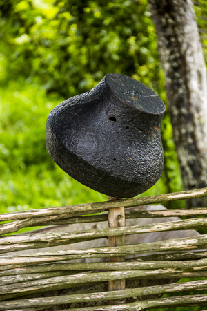 the old big black holey pot on the wicker fence Stock Photo