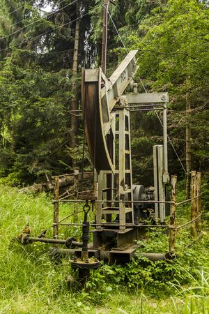 old fashioned oil pump in the pine forest Stock Photo