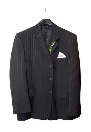 traje: Chaqueta de traje colgado en una percha con una flor en el ojal en el lugar en el fondo blanco Foto de archivo