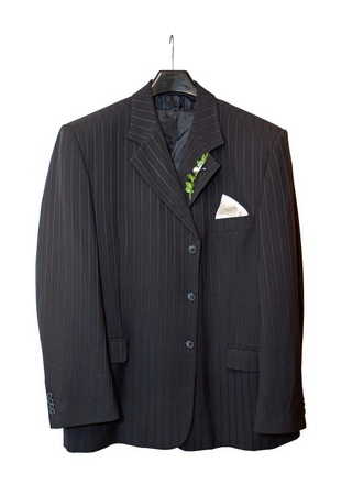 Suit jacket hanging on a hanger with a boutonniere in place on white background  photo