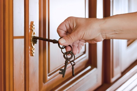 locking up: Locking up or unlocking the door with a key in hand Stock Photo