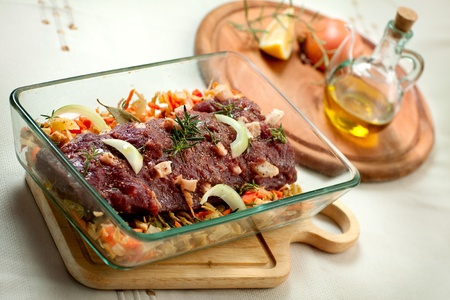 fresh raw deer meat in a glass bowl photo