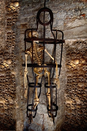 A skeleton chained in the metal cage in a cave photo