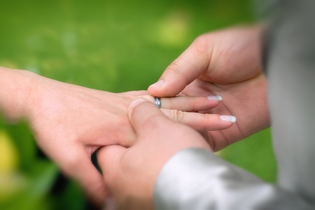 wedding vows: Groom putting a ring on brides finger during wedding ceremony
