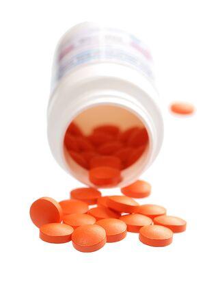 pilule: Abrir una botella de píldoras derramadas. Aislado sobre fondo blanco Foto de archivo