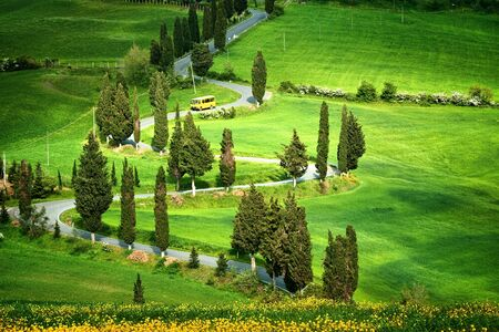 Beautiful landscape in Tuscany with sinuous road and yellow bus photo