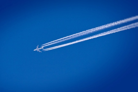 Flying airplane on the blue sky leaving white lines behind photo