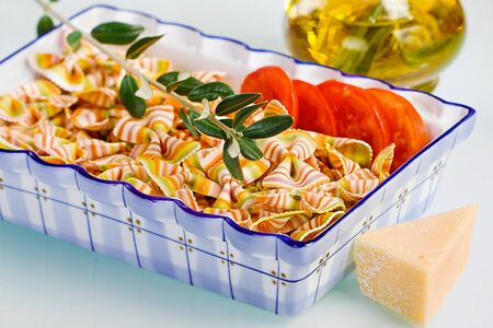 Beauty colored of pasta with tomato, olive and cheese. photo