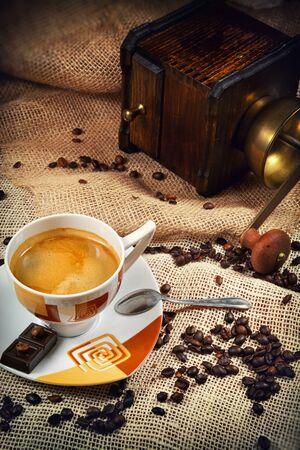 hot temper: Taza de caf� rodeado de granos de caf� y caf� molino-en el fondo Foto de archivo