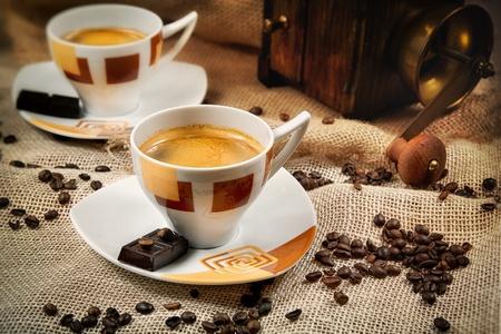 hot temper: Taza de café rodeado de granos de café y café molino-en el fondo Editorial
