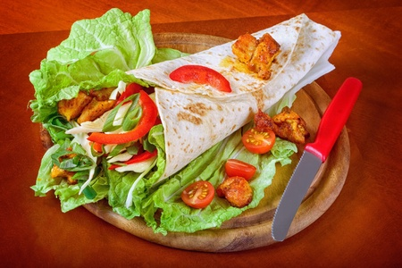Healthy summer meal, grilled chicken and vegetables wrapped in a whole wheat tortilla photo