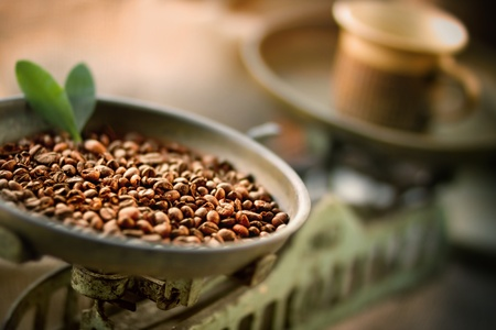 Cup of coffee with beans on old balance scale photo