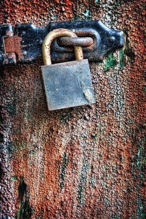 Old rusty padlock hanging on the door photo