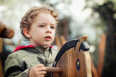 cute little boy playing on the playground outdoor  photo