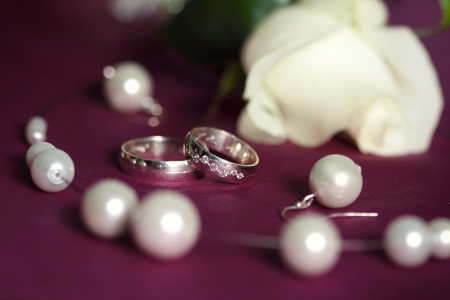 silver wedding anniversary: Pair of wedding rings with white roses and beads on purple background Stock Photo